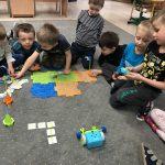Siedmioro dzieci siedzących na dywanie w sali przedszkolnej. Jeden chłopiec trzyma w rękach pilota. Przed dziećmi znajduje się robocik, trzy wieżyczki, trasa ułożona z kolorowych puzzli oraz fiszek
