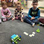 Pięcioro dzieci siedzących na dywanie w sali przedszkolnej. Dziewczynka trzyma w rękach pilota. Chłopiec trzyma w rękach dwie, kolorowe piłeczki. Przed dziećmi, znajduje się robot, ułożona z fiszek trasa oraz wieża.