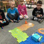 Pięcioro dzieci siedzących na dywanie w sali przedszkolnej. Jeden chłopiec trzyma w rękach pilota. .Przed dziećmi, znajduje się ułożona z puzzli trasa, oraz robot, wieżyczka, koło i plastikowe, kolorowe kostki.