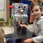 Chłopiec siedzący na dywanie w sali przedszkolnej. Za nim stoi robot wykonany z materiałów plastycznych.
