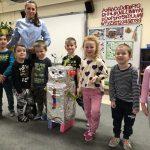 Siedmioro dzieci stojących w rzędzie w sali przedszkolnej. Za dziećmi stoi pani nauczycielka. Przed dziećmi stoi robot wykonany z materiałów plastycznych.