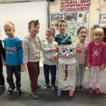 Ośmioro dzieci stojących w rzędzie w sali przedszkolnej. Przed dziećmi stoi robot wykonany z materiałów plastycznych.