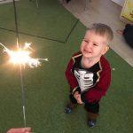 Chłopiec stoi na dywanie i patrzy na płonący zimny ogień.