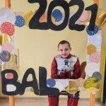 Chłopiec w przebraniu robota siedzi na krześle za dużą ramką ozdobioną koilorowymi kołami i napisem BAL 2021