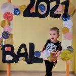 Chłopiec w przebraniu pirata stoi za dużą ramką ozdobioną koilorowymi kołami i napisem BAL 2021