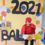 Chłopiec w przebraniu ( peleryna i czapka czerwona) siedzi na krześle za dużą ramką ozdobioną koilorowymi kołami i napisem BAL 2021