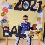 Chłopiec w przebraniu policjanta siedzi na krześle za dużą ramką ozdobioną koilorowymi kołami i napisem BAL 2021