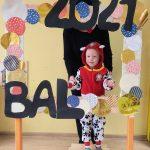 Chłopiec w przebraniu stoi za dużą ramką ozdobioną koilorowymi kołami i napisem BAL 2021