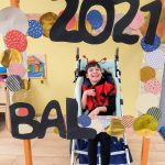 Dziewczynka w przebraniu biedronki siedzi na wózku za dużą ramką ozdobioną koilorowymi kołami i napisem BAL 2021