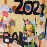 Chłopiec w przebraniu siedzi na wózku za dużą ramką ozdobioną koilorowymi kołami i napisem BAL 2021