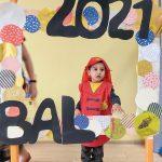 Chłopiec w przebraniu strażaka stoi za dużą ramką ozdobioną koilorowymi kołami i napisem BAL 2021