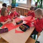 4 dzieci siedzi przy stole. W rękach trzymają kartki i nożyczki