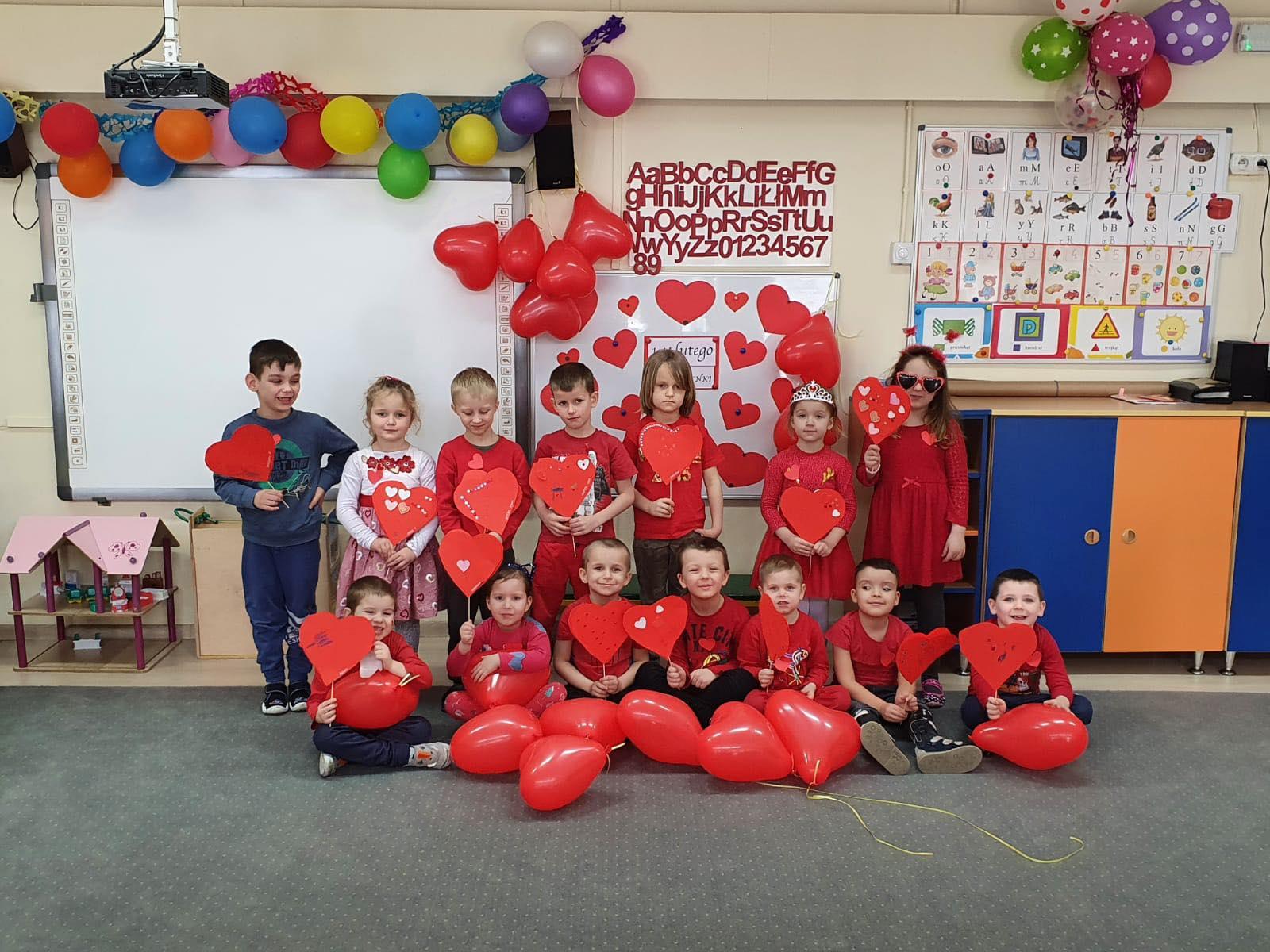 Grupa dzieci ustawiona w 2 rzędzach jeden stoi, drugi siedzi. W rękach trzymają balony.
