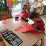 2 dzieci siedzi przy stole. W rękach trzymają kartkę i nożyczki