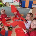 5 dzieci siedzi przy stole. W rękach trzymają kartki i nożyczki