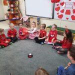 Dzieci siedzą w kole. Jedna dziewczynka podaje chłopczykowi balon w kształcie serca.