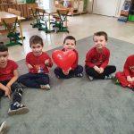 Dzieci siedza na dywanie w kole. Jedno dziecko trzyma balon w kształcie sercas.