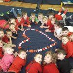 Dzieci leżą na dywanie na brzuchu wokoło ułożonego serca składającego się w wielu małych serduszek