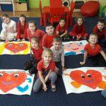 Na dywanie leżą kartki z namalowanymi sercami przez dzieci. Dzieci siedzą obok nich.