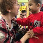 Uśmiechnięty chłopiec patrzy się na nauczycielkę.