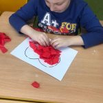 Chłopiec siedzi przy stoliku. Przed nim leży kartka z konturem serca, które wykleja bibułą.