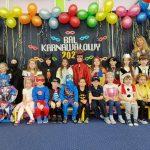 Dzieci są ustawione w 2 rzędach. Jeden stoi , 2 siedzi. Dzieci przebrane sa kolorowe przebrania. Nad nimi wiszą kolorowe balony.