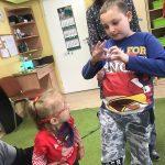 Chłopiec stoi obok dziewczynki i pokazuje jej serce ułożone z dłoni. Dziewczynkę trzyma nauczycielka.