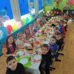 Dzieci siedzą przy stole.