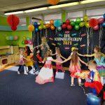 Przebrane dzieci tańczą w dużym kole.