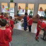 Dzieci stoją w parach na dywanie. Trzymają się za ręce a po środku brzucha trzymają balony w kształcie serca