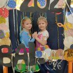 2 dziewczynki trzymają się za ręce. Przed nimi stoi ramka z napisem bal 2021 i kolorowymi kółkami.