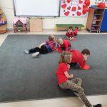 Kilkoro dzieci leży na dywanie.