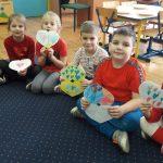 2 dziewczynki i 2 chłopców siedzi na dywanie. W rękach trzymają papierowe serduszka.