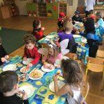 Dzieci siedzące przy stolikach w sali przedszkolnej. Na stolikach znajdują się talerze oraz ciastka i cukierki. Każde dziecko ma u.brany karnawałowy strój
