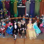 Grupa dzieci siedzących w kole na krzesłach w sali przedszkolnej. Dzieci ubrane są w karnawałowe stroje. W tle, na ścianie znajduje się dekoracja składająca się z balonów oraz kolorowych pasków bibuły.