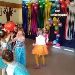 Dzieci tańczące w parach w sali przedszkolnej i odbijające balony. Dzieci mają ubrane karnawałowe stroje. W tle, na ścianie znajduje się dekoracja złożona z balonów i kolorowych pasków bibuły.