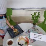 Chłopiec ubrany w fartuszek i czapkę kucharską siedzący przy stoliku i układający na talerzu owocową sowę. Na stole znajdują się talerze z owocami.