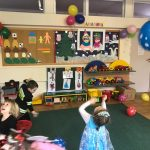 Troje dzieci ubranych w strój karnawałowy i bawiących się balonami w sali przedszkolnej.