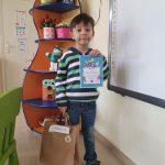Chłopiec stojący w sali przedszkolnej i trzymający w ręku dyplom oraz papierową torbę.