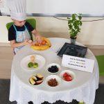 Chłopiec ubrany w fartuszek i czapkę kucharską siedzący przy stoliku i obierającym mandarynkę. Na stole znajdują się talerze z owocami.