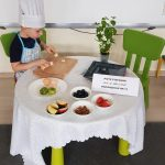 Chłopiec ubrany w fartuszek i czapkę kucharską siedzący przy stoliku i krojącym banana. Na stole znajdują się talerze z owocami.