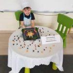 Chłopiec ubrany w fartuszek i czapkę kucharską, siedzący przy stole, na którym znajduje się talerz z owocową sową oraz wizytówka z imieniem i nazwiskiem chłopca oraz nazwą przedszkola.