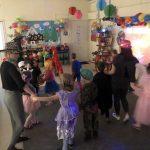 Grupa dzieci tańczących w sali przedszkolnej. wraz z trzema paniami. Dzieci ubrane są w kostiumy karnawałowe, panie mają na głowach kapelusze.