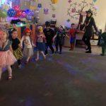 Grupa dzieci trzymających się za ręce i tańczących w kole wraz z panią mającą na głowie kapelusz.