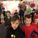 Na pierwszym planie znajduje się czterech chłopców ubranych w karnawałowe kostiumy. Na drugim planie znadują się dwie panie w kapeluszach oraz czworo dzieci ubranych w karnawałowe stroje.