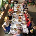 Grupa dzieci siedząca przy stołach w sali przedszkolnej. Na stołach znajduje się słodki poczęstunek, dzieci ubrane są w karnawałowe stroje.
