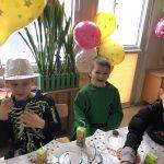 Trzech chłopców siedzących przy stole w sali przedszkolnej. Chłopcy ubrani są w karnawałowe stroje. Chłopiec po lewej stronie trzyma w ręce balona.