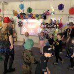Grupa dzieci tańczących w rozsypce w sali przedszkolnej wraz z dwoma paniami. Dzieci ubrane są w kostiumy karnawałowe. Panie mają na głowach kapelusze.