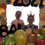 Dwie dziewczynki pozujące do zdjęcia w ramce ozdobionej balonami. Dziewczynki są ubrane w karnawałowe stroje.