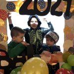 Trzech chłopców pozujących do zdjęcia w ramce ozdobionej balonami. Chłopcy ubrani są w kostiumy karnawałowe.